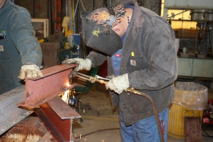 Man using gas torch to weld metal frame