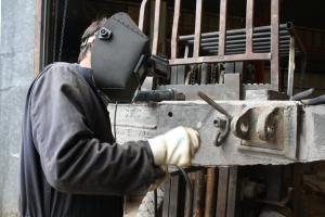 Restoration worker Erik Young welding on the tender truck frame for the Sierra #3.