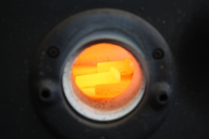 Red-hot rivets visible through the porthole of the forge.