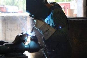 Foreman Erik Youg welding on brake line hardware.