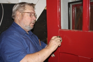 Cliff Hughs adjusts hardware on the door of the caboose.