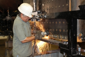 Greg Kelsch grinds off a few rivet heads that were interfering with the fit of the boiler to the frame.