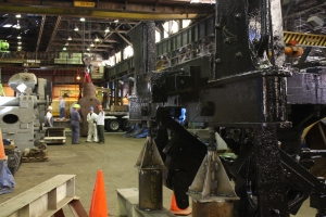 The shop crew conducts a short job briefing to plan for movement of the boiler.  Chassis can be seen in the foreground.