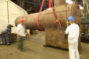 Jim Bayes (at right, with pendant in hand) guides the boiler into place.