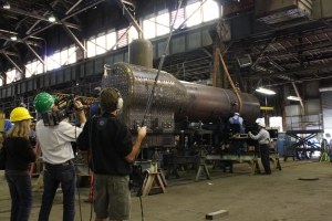 Al DiPaulo and George Sapp adjust the rigging for the final lift of the boiler, while the documentary film crew looks on.
