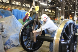 Lisa Smithson operates the crane while Leonard Jones rocks the box back and forth over the dye-covered axle.  An examination of the stained bearing surface indicates what still needs to be scraped and the process is repeated until the surface is perfectly married.