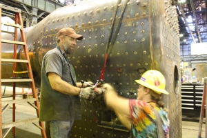 Phil Hard and DJ Ponder adjust a mag drill to ream holes for the running board studs.