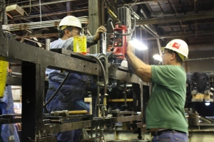 Al DiPaulo and Leonard Jones adjust the mag drill for reaming the furnace bearer strap holes into the frame.  One of the last items needed prior to the final fitting of the boiler.