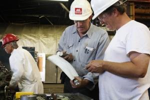 George Sapp reviews bolt specifications with Randy Mathews, while Jim Bays machines bolts in the background.