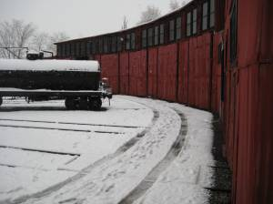 A lonely tank car in front of the roundhouse.