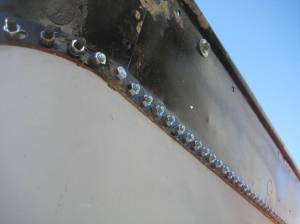 Coal board is held on with bolts until rivets can be applied.