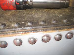 The top of the tender is preserved from the original tender.  Here the old rivets can be seen alongside the new.