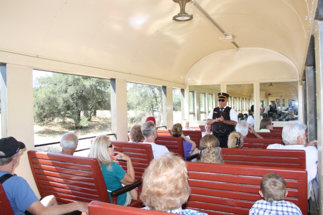 A view of the open sides on the 599 Mountain Observation car, with car host and passengers