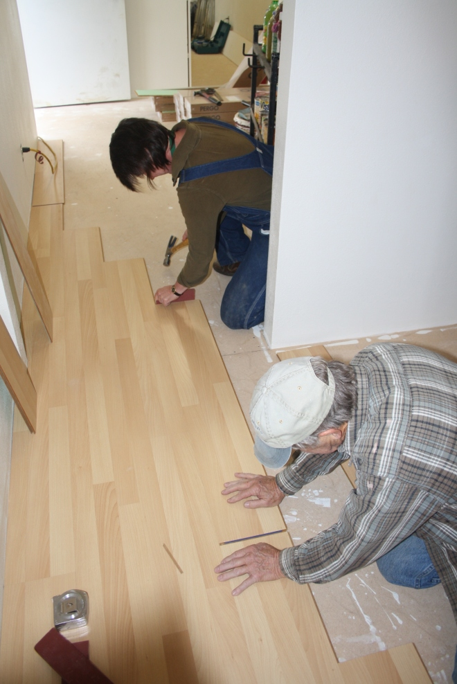 Curator Lisa Smithson and Volunteer Lead Dave Deutch are installing floor covering to refurbish a space for a volunteer library and curatorial work space.