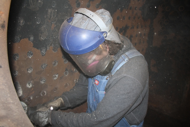In preparation for installation of new firebox bricks on the No. 2, volunteer James Kennard grinds out interior.