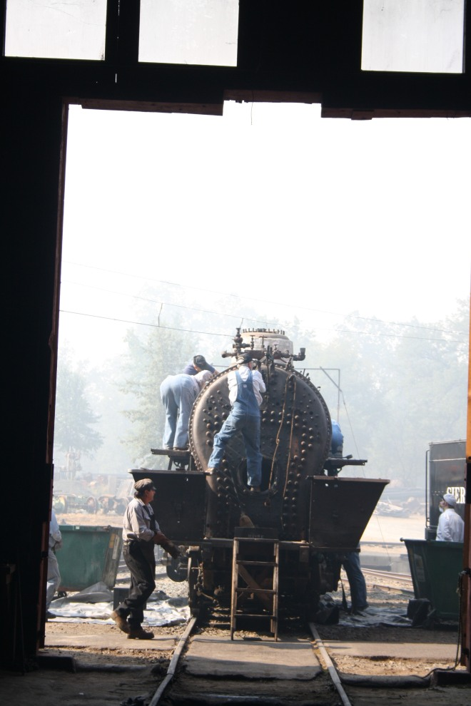 Volunteers swarm the locomotive and make quick work of the task