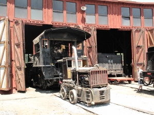 "No. 28, tender removed,  being pulled out of its stall by ""the little engine that could"""