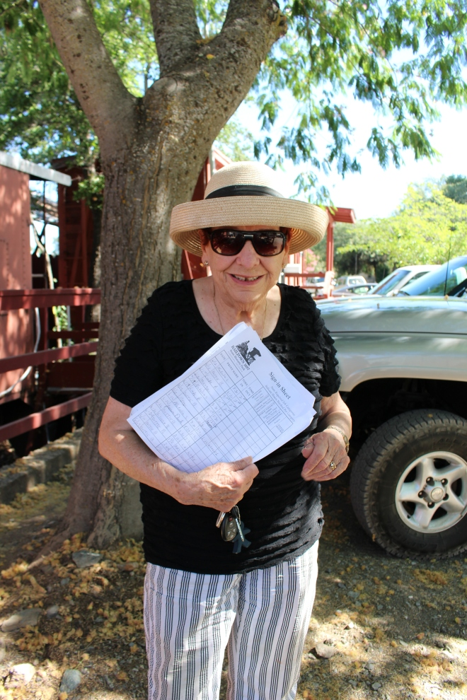 Volunteer Laverne collecting sign in sheets to record volunteer hours