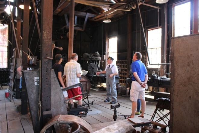 Volunteer Tim leading a tour of the historic machine shop for park visitors.